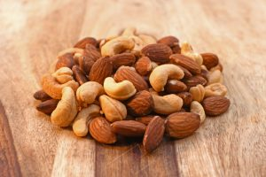 Salted mixed almond and cashew nuts on cutting board